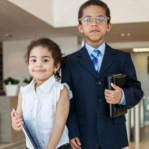 Young children in business clothes in the business center with c